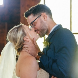 Bride and groom exchange as kiss after vows during their Diary Barn wedding ceremony coordinated by Magnificent Moments Weddings