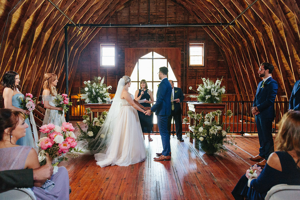 Bride and groom exchange vows during their wedding ceremony at the Diary Barn coordinated by Magnificent Moments Weddings