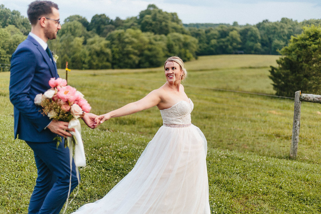 Bride leads groom through the grounds of the Diary Barn during their spring wedding captured by Alivia Photography