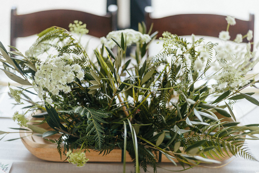 Leafy greens and a wooden tray create an organic centerpiece created by Nkemdi Thompson for a spring wedding a The Diary Barn
