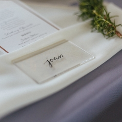 Glass tiles serve as place settings that set on top of linen napkins and a pale blue linen, rented from creative solutions and coordinated by Magnificent Moments Weddings