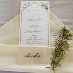 Place setting with linen napkin, detailed menu card, and garden greenry show off rustic details at a Dairy Barn Wedding