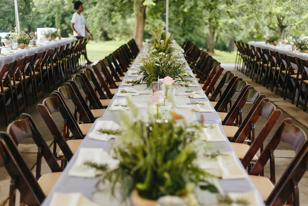Table setting for a spring wedding at The Dairy Barn, including blue linens and dark brown chairs rented from Creative Solutions and coordinated by Magnificent Moments Weddings