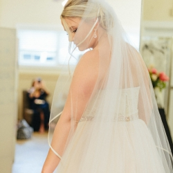 Bride poses with stunning veil before her spring wedding at The Diary Barn coordinated by Magnificent Moments Weddings