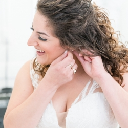 Bride puts on her earrings before walking down the aisle during her wedding coordinated by Magnificent Moments Weddings