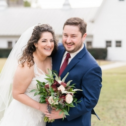 Bride and groom smile for the camera in front of their stunning wedding venue The Dairy Barn