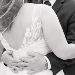 Jenny Williams Photography captures the stunning lace details of a brides dress as she embraces her groom