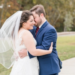 Bride and groom share a romantic moment before walking down the aisle during their wedding coordinated by Magnificent Moments Weddings