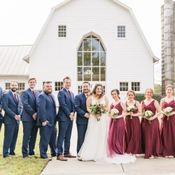 The Dairy Barn serves as a stunning backdrop for bridal party photos during a fall wedding captured by Jenny Williams Photography