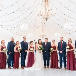 Bride and groom pose with their bridal party in the reception space of the Dairy Barn during their wedding coordinated by Magnificent Moments Weddings