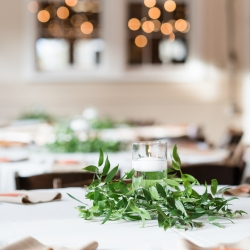 Simple centerpieces created by Buy the Bunch feature floating candles and greenery for a wedding at The Diary Barn