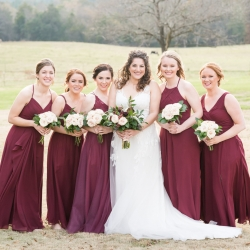 Bride poses with her bridesmaids wearing stunning red gowns during her wedding day at The Diary Barn
