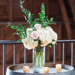 Stunning ceremony florals feature while hydrangeas and soft pink roses created by Buy the Bunch