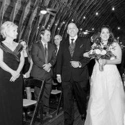Bride is escorted down the aisle by her father during her wedding ceremony at The Dairy Barn