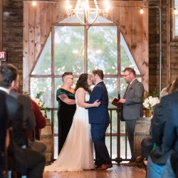 Bride and groom share a kiss during their wedding ceremony at The Dairy Barn planned and coordinated by Magnificent Moments Weddings