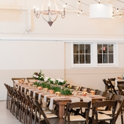 Rustic farmhouse tables and dark wooden chairs rented from Creative Solutions were the perfect setting for a wedding reception at The Dairy Barn