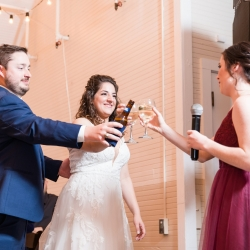 Bride and groom raise a glass as they are toasted during their fun wedding at The Diary Barn