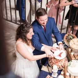 Bride and groom share a piece of cake made by Family Catering during their fun wedding at The Dairy Barn