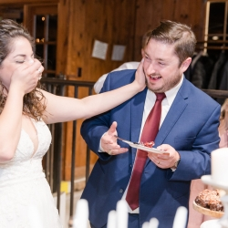 Bride and groom share a fun moment as their cut their cake made by Family Catering