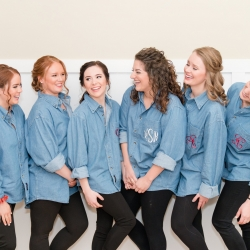 Bride poses with her bridesmaids wearing matching monogrammed shirts as they get ready for her wedding at The Diary Barn