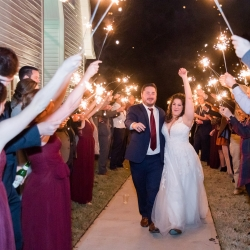 Bride and groom exit through a sea of sparklers after their wedding at The Dairy Barn