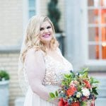 Bride posing with bridal bouquet designed by Whats Up Buttercup wearing a beautiful lace detail wedding dress from New York Bride and Groom