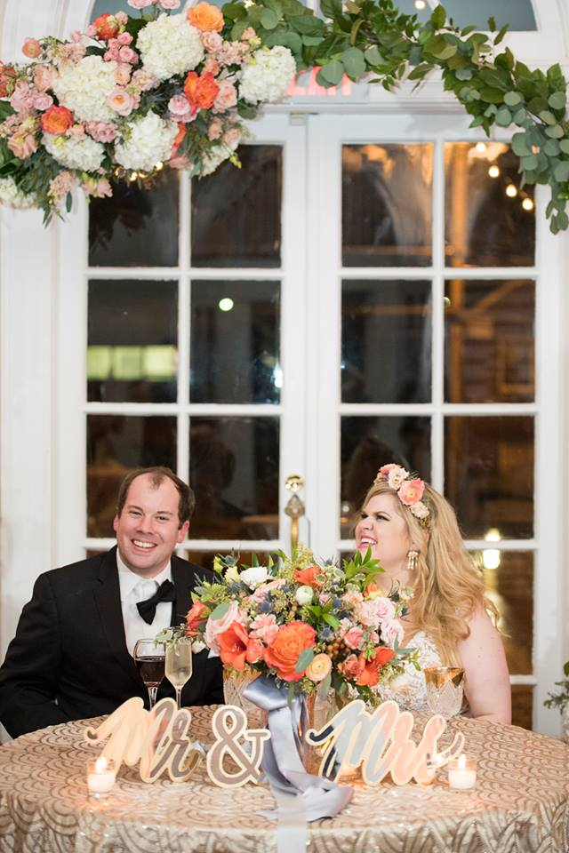 Bride and groom at sweetheart table under amazing floral details by What's Up Butter Up at Separk Mansion Wedding