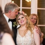 Bride and father embrace at wedding reception coordinated by Magnificent Moments Weddings