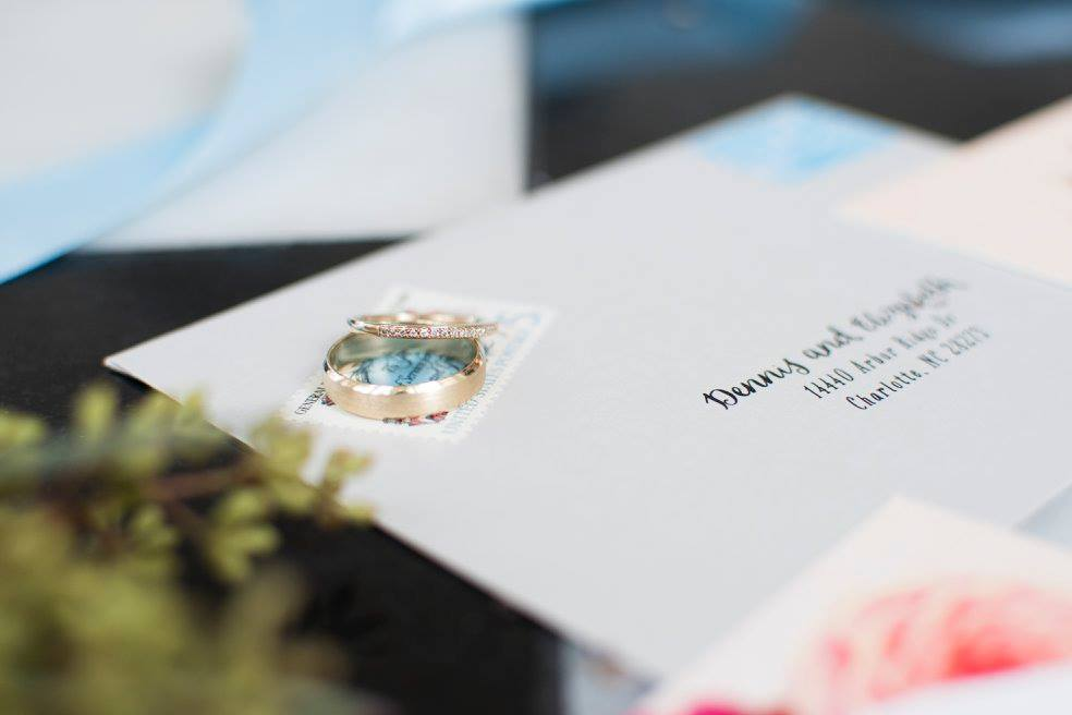 Detail shot of wedding rings and invitation captured by Soussou Productions