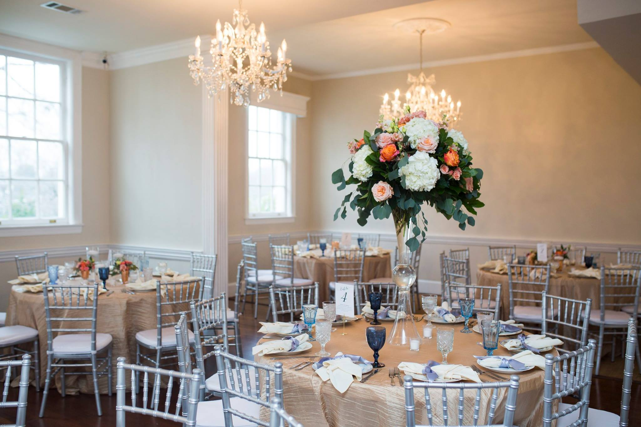 Wedding reception tables set with blush linens and vintage dishes from Evermore accented with tall florals designed by What's Up Buttercup