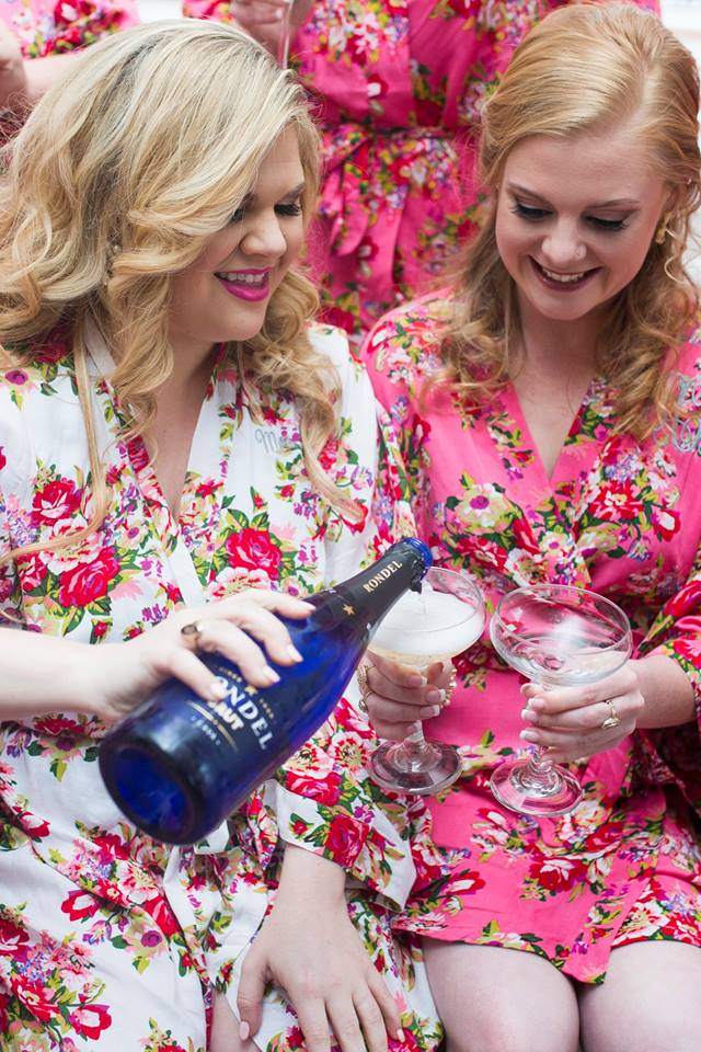 Bride with bridesmaids sharing champagne in matching getting ready outfits captured by Soussou Productions