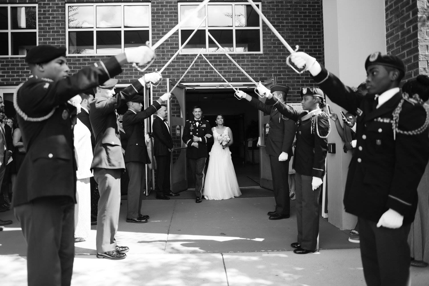 bride and groom having a military salute exit