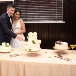 bride and groom cutting their wedding cake with a military sword