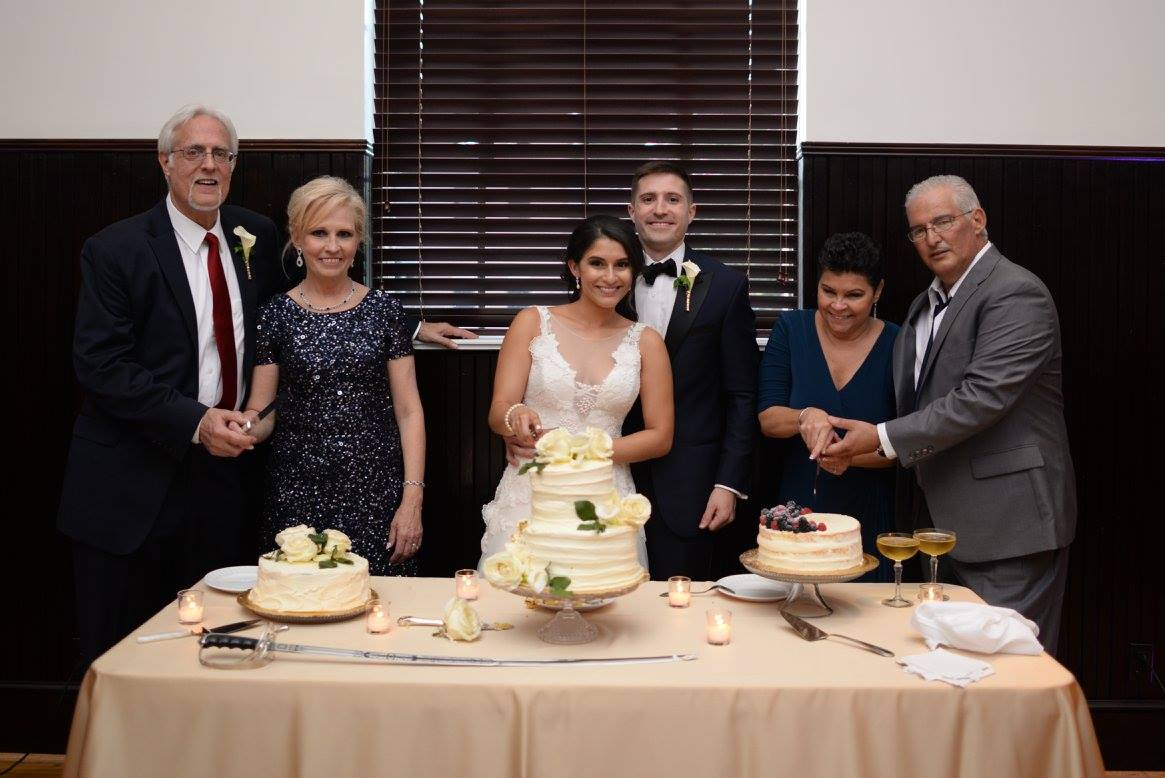 Parents cutting cakes with the bride and groom