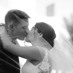 Bride and groom kissing under a wedding veil