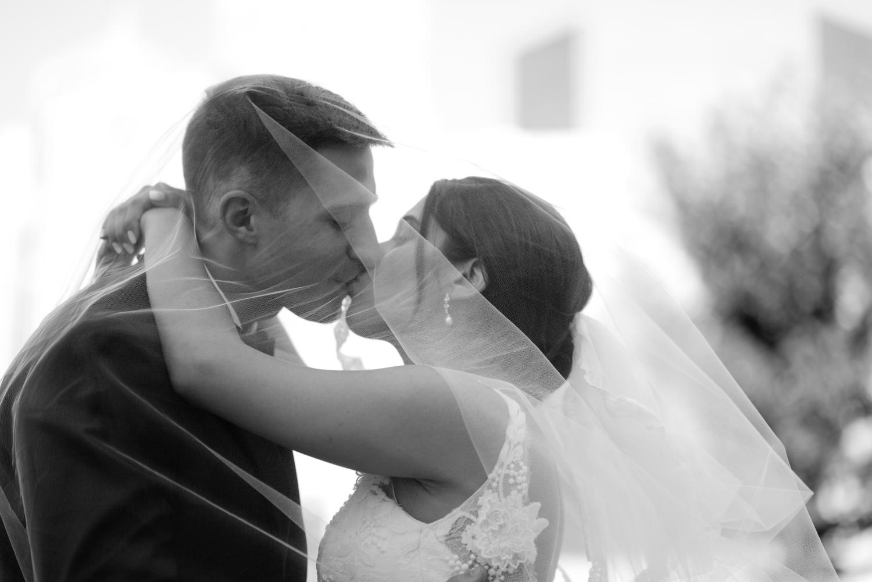 Bride and groom kissing under a wedding veil