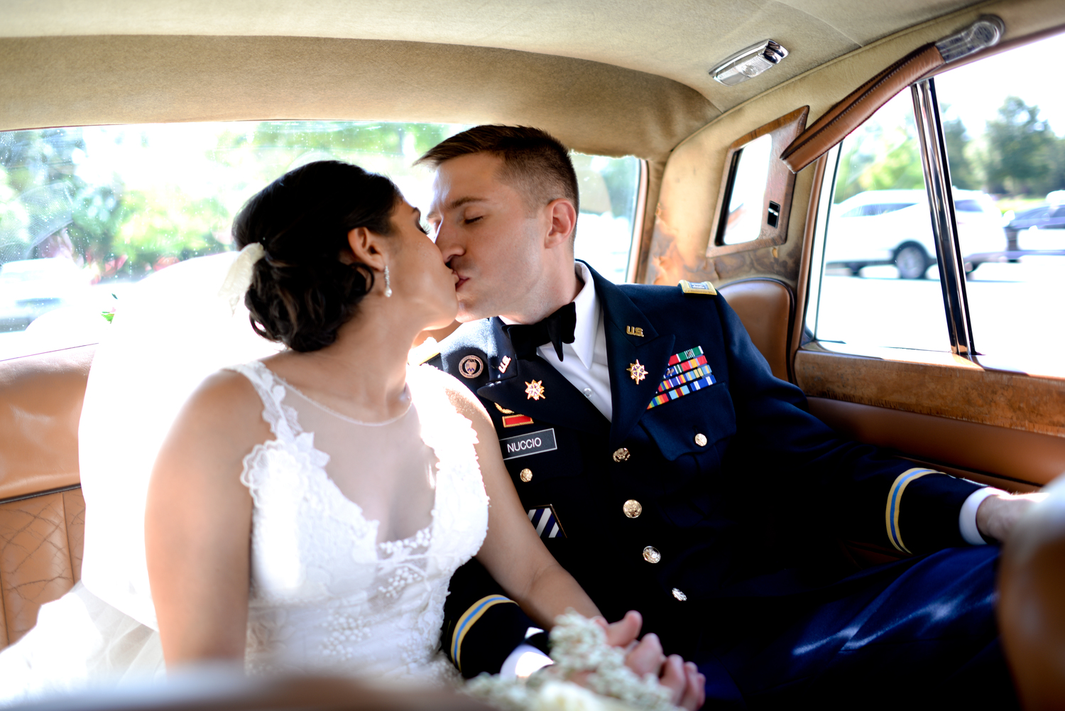 bride and groom kissing in the back of their classic car