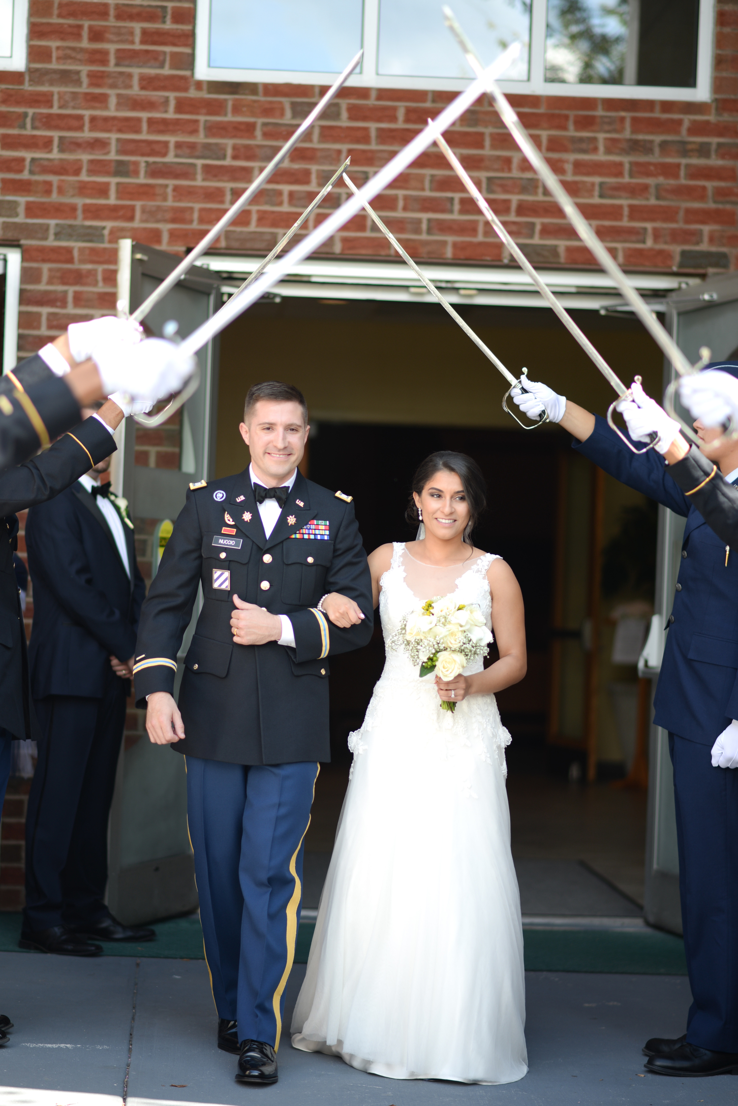 Bride and groom exiting under military swords at St. Matthew Catholic Church
