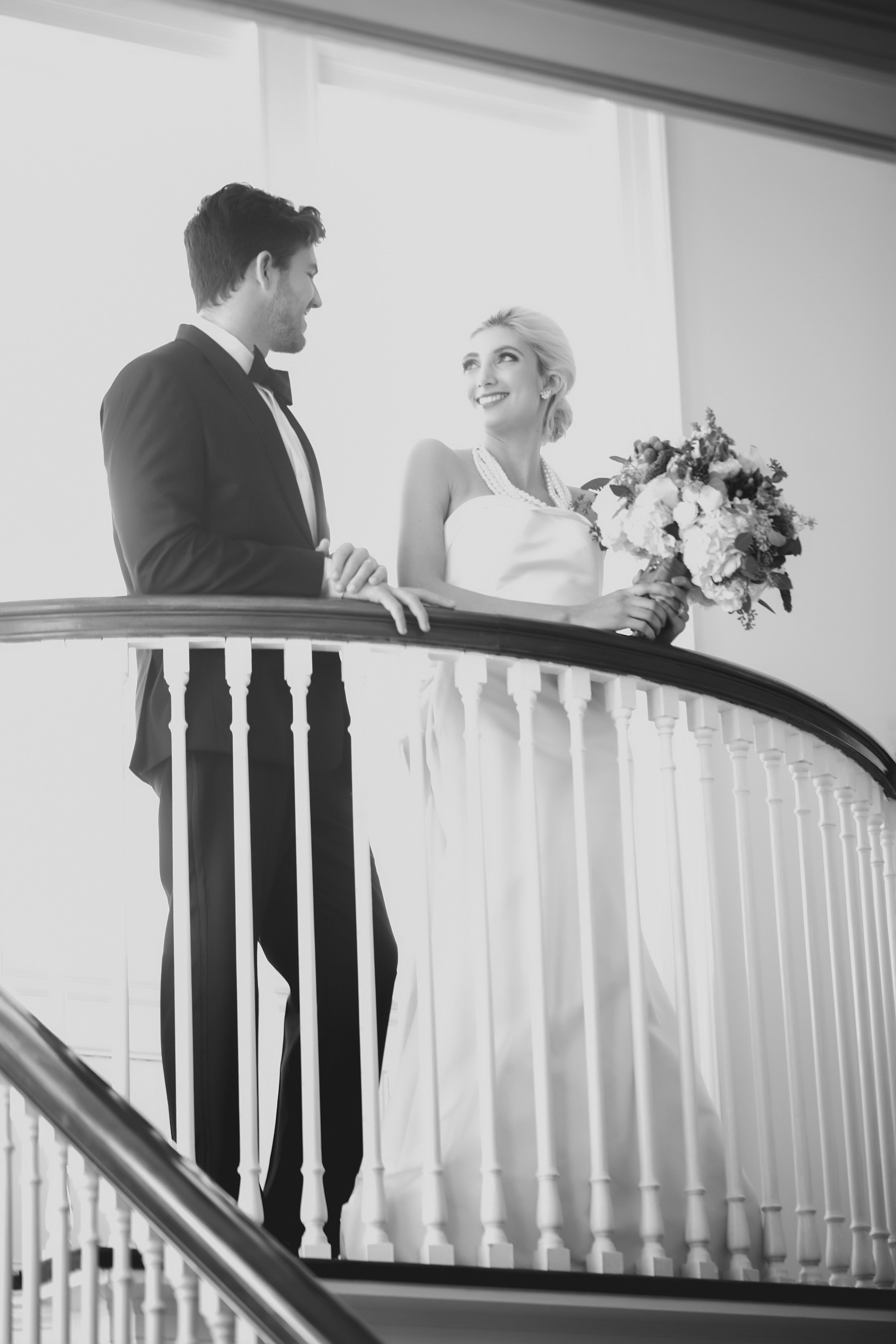 Bride and groom look over their wedding reception at the Separk Mansion designed by Magnificent Moments Weddings