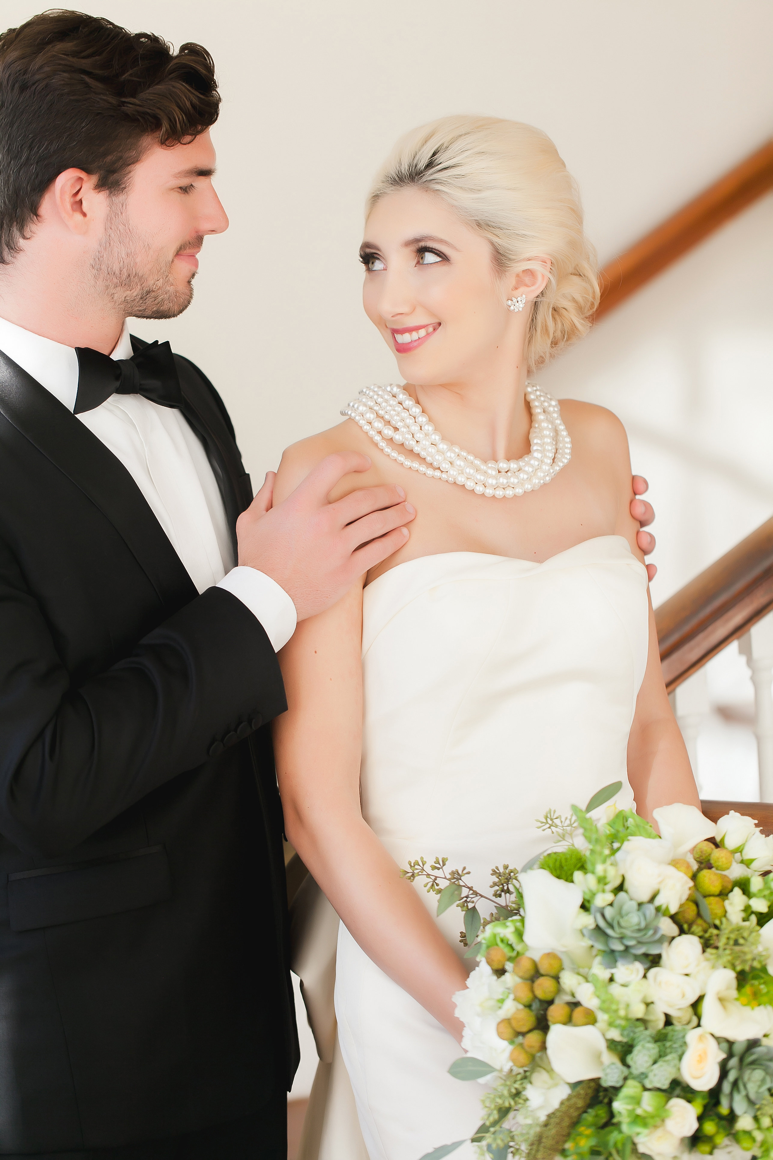 Groom embraces bride before their Separk Mansion wedding as she holds a stunning all white bouquet by Chelish Moore