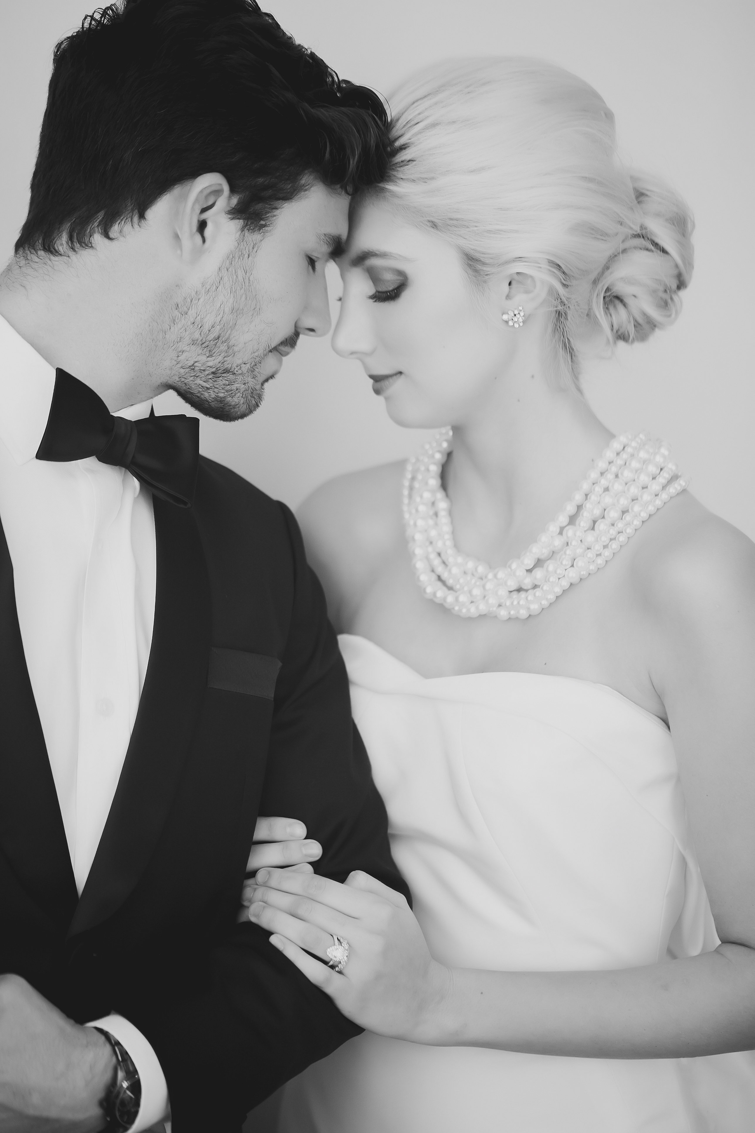 Bride embraces groom with stunning hair and makeup by Beauty Asylum