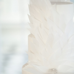 Delicate white wedding cake with feather detail and silver accents created by Sky's the Limit Bridal Sweets captured by Casey Hendrickson Photography