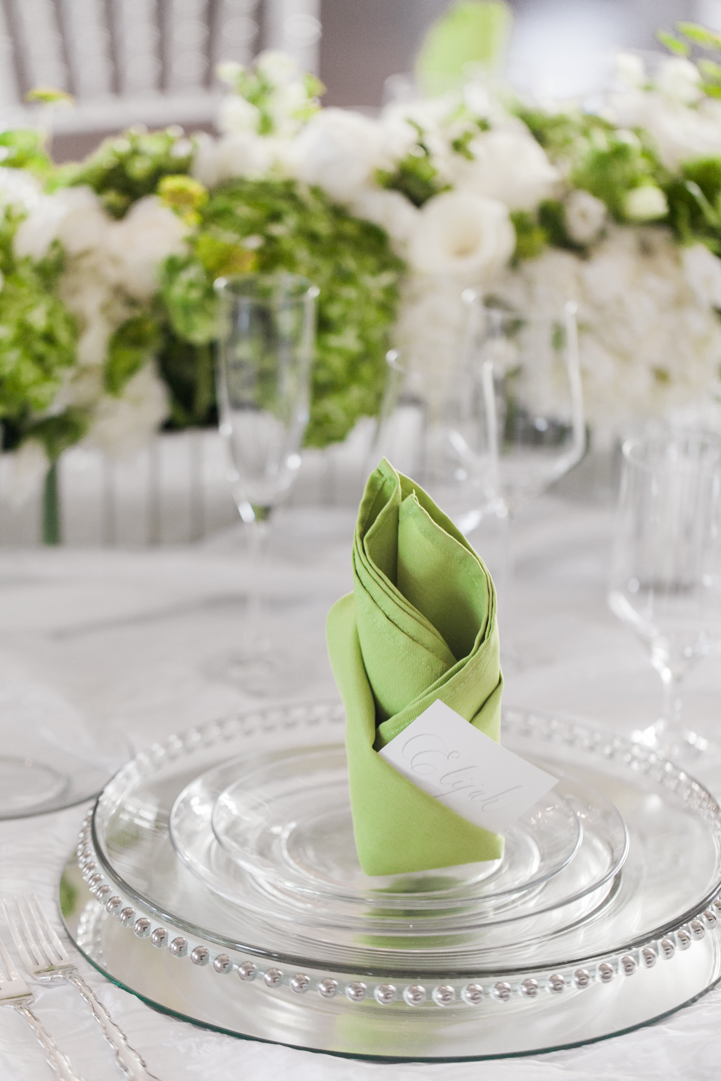 Table setting with green accent napkins and stunning glass charges for a wedding designed by Magnificent Moments Weddings
