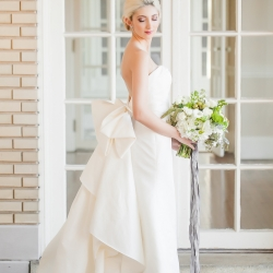 Bride poses in stunning white gown with bow detail from Paige and Elliot before her wedding at Separk Mansion