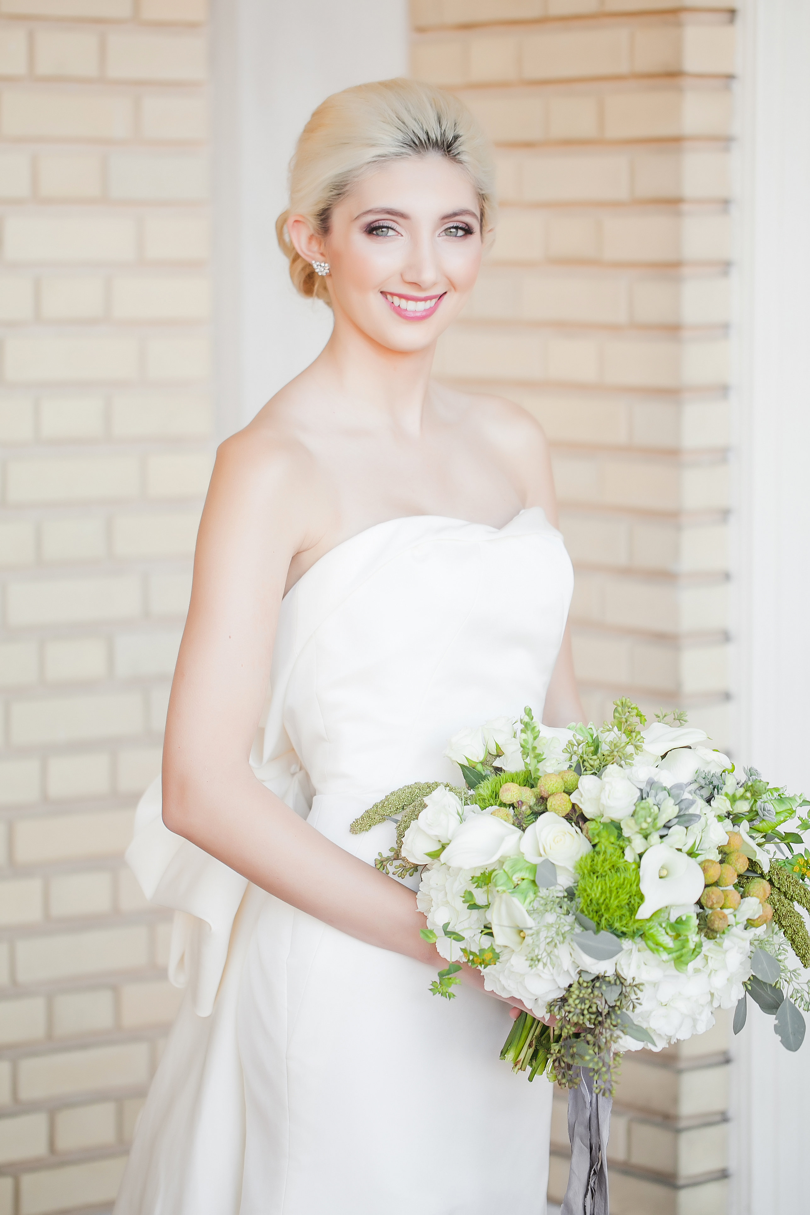 Bride wearing stunning dress from Paige and Elliot holding white bridal bouquet designed by Chelish Moore