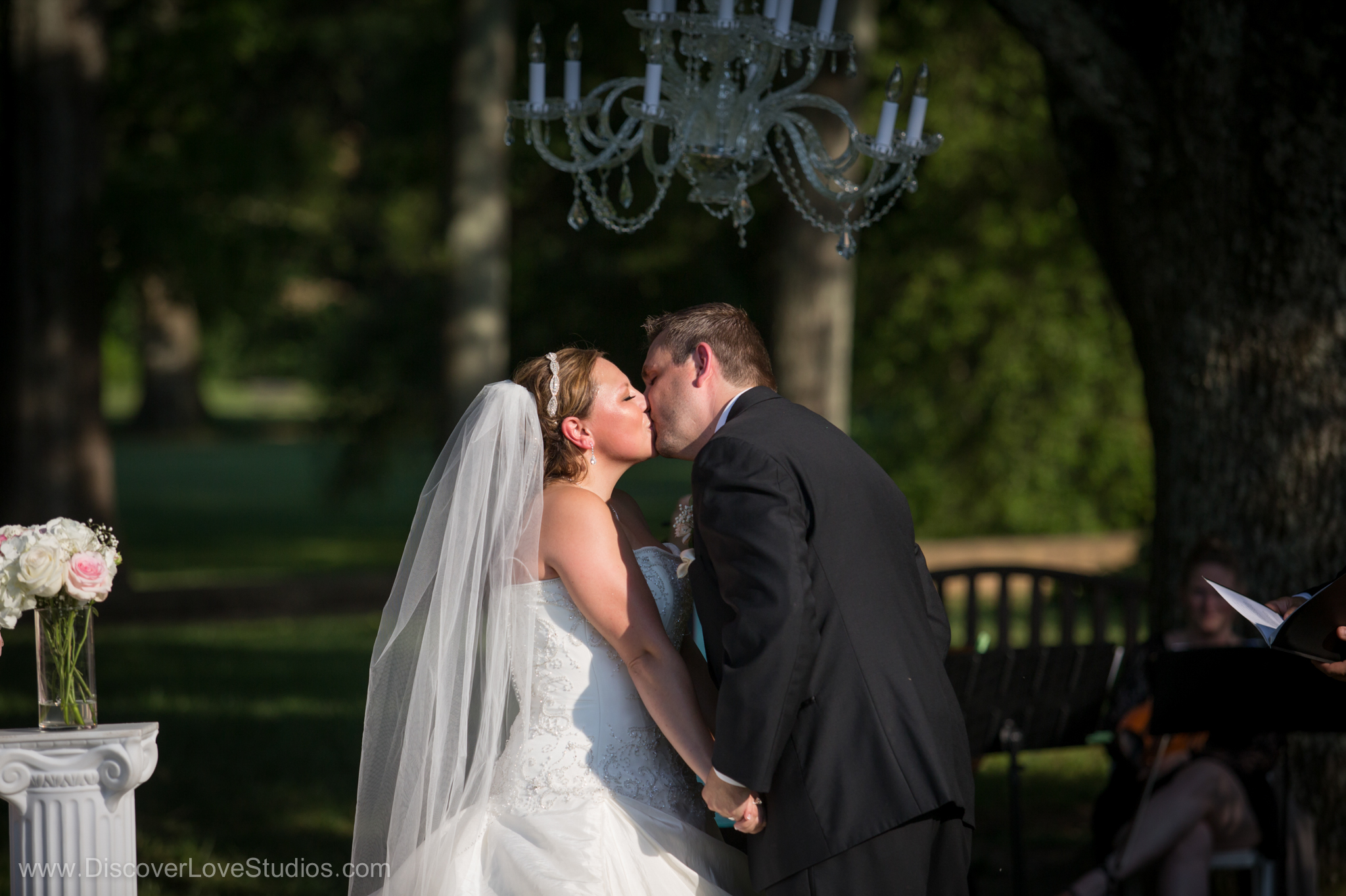 bride and groom kissing during their ceremony under a chandelier from Cooke Rentals.