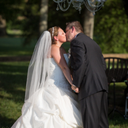 Bride and groom kissing during their ceremony at the Mint Museum Randolph.