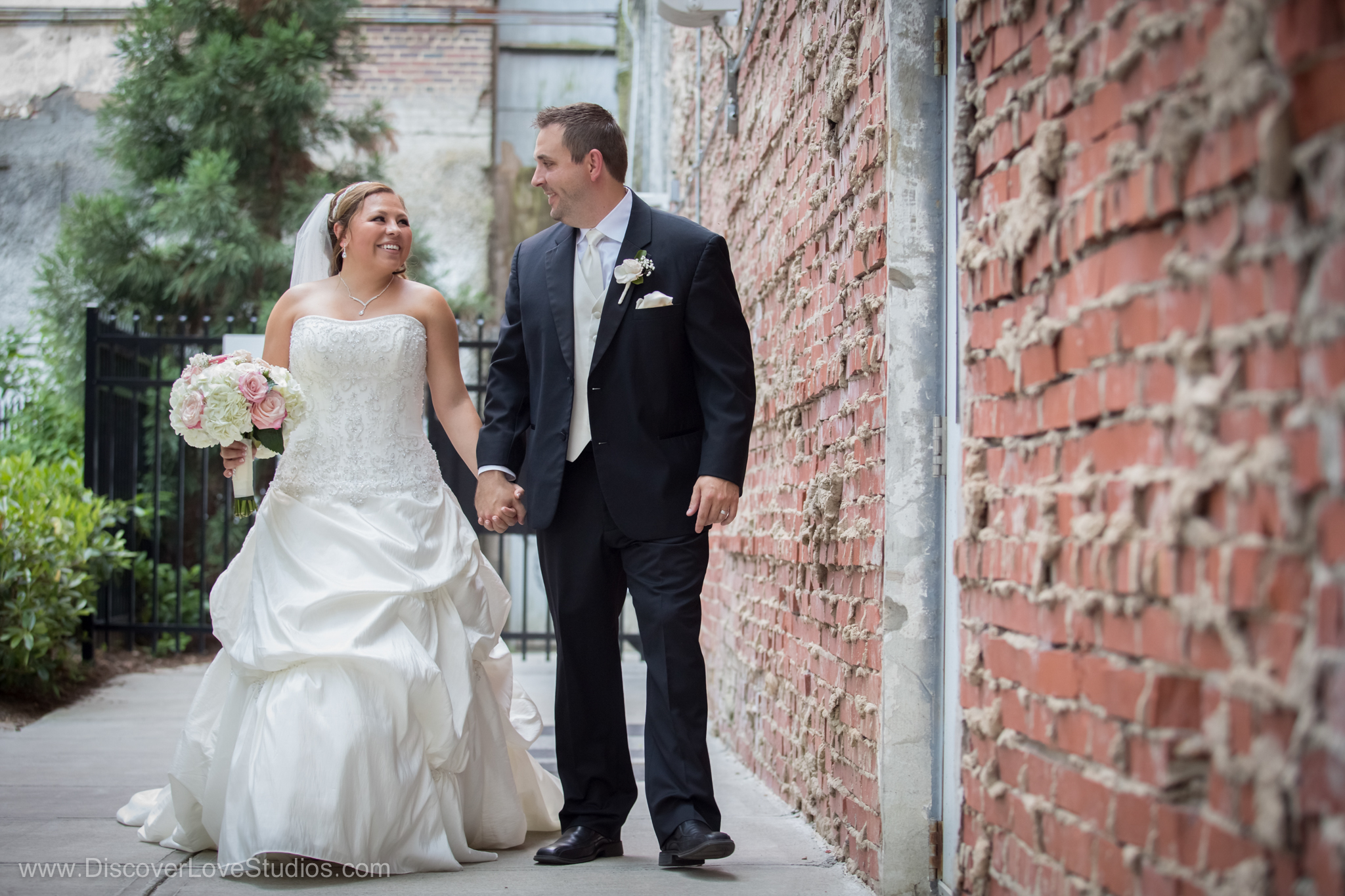 Bride and groom walking hand in hand by a brick wall in Uptown Charlotte.