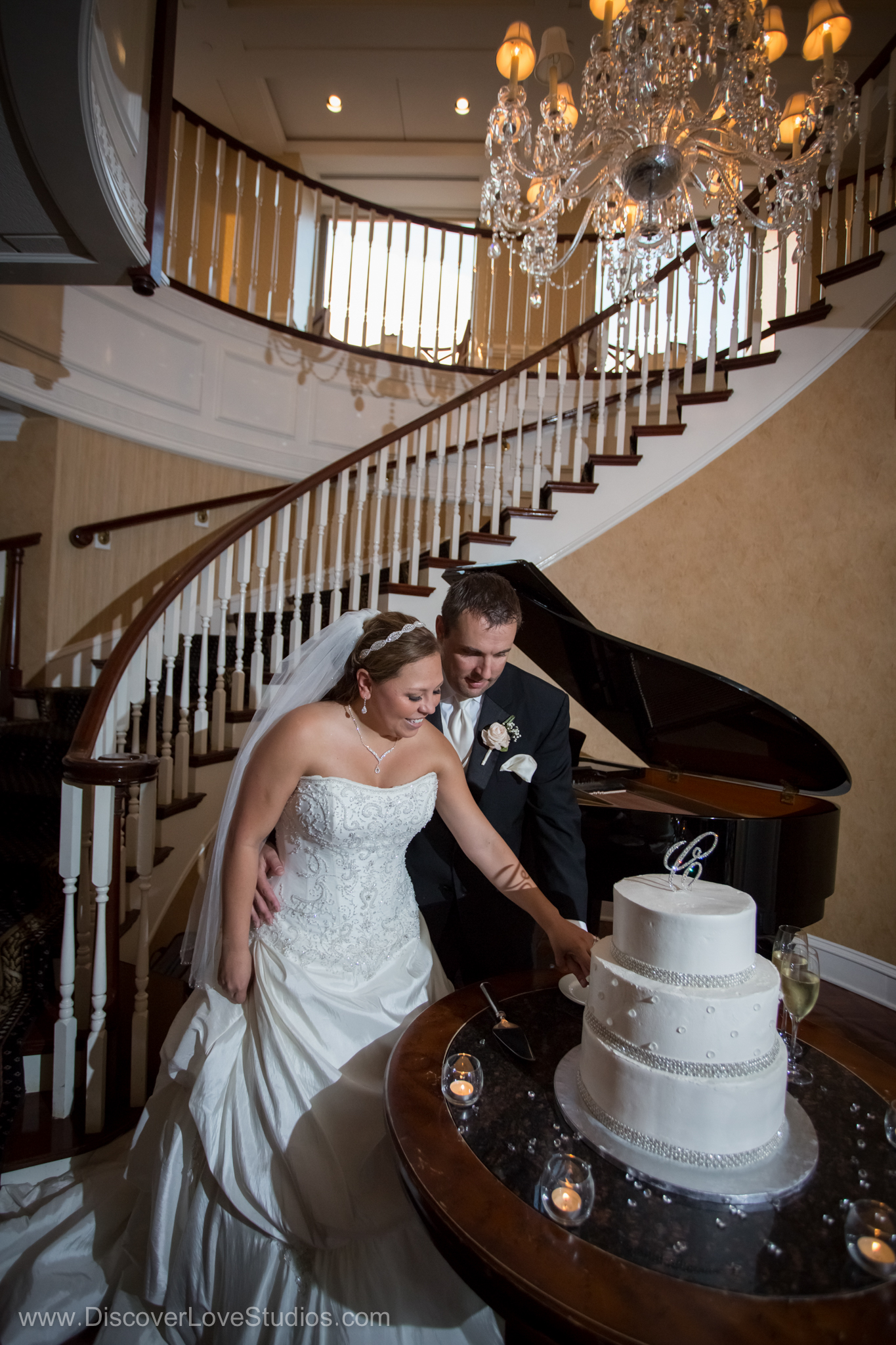 Bride and groom standing near the ornate staircase with a grand piano cutting into their wedding cake.