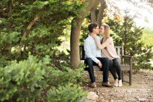 Charlotte Independence Park engagement shoot, park setting, kiss on a bench, captured by Old South Studios, wedding coordination by Magnificent Moments Weddings